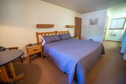 This chalet style handicap room has a king bed and a table with seating for two.