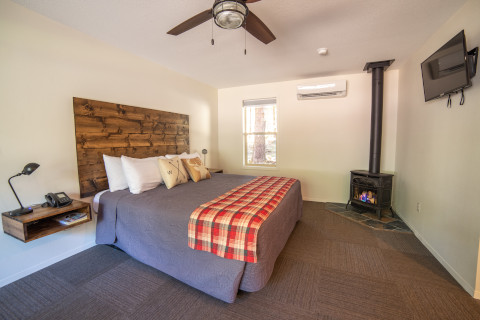 A studio cabin with a gas fireplace. This cabin also has an A/C heater unit in it. A wall mounted TV is at the foot of the king bed.