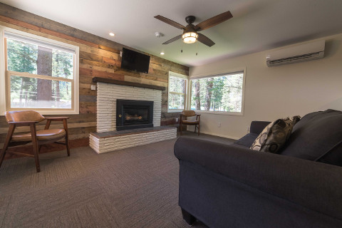 A large living room with a pull out couch in front of a gas fireplace. This cabin has an A/C heater unit as well as a ceiling fan for extra air circulation. There are lots of windows to let in light, and to view the activities going on around outside.